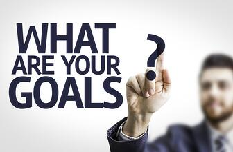 Business man pointing to transparent board with text What are Your Goals?