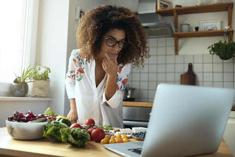 business woman in kitchen on laptop